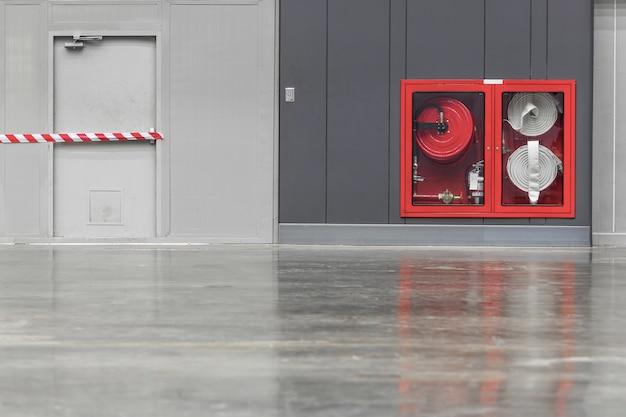 Hidrante com mangueiras de água e fogo extinguir equipamentos na parede em um corredor.