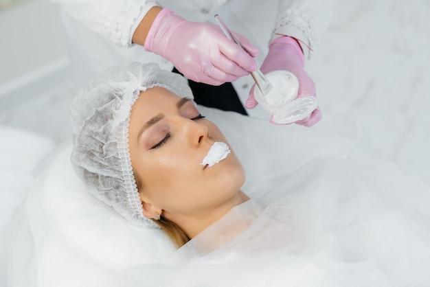 Hidratação dos lábios durante um procedimento cosmético em uma jovem. cosmetologia.