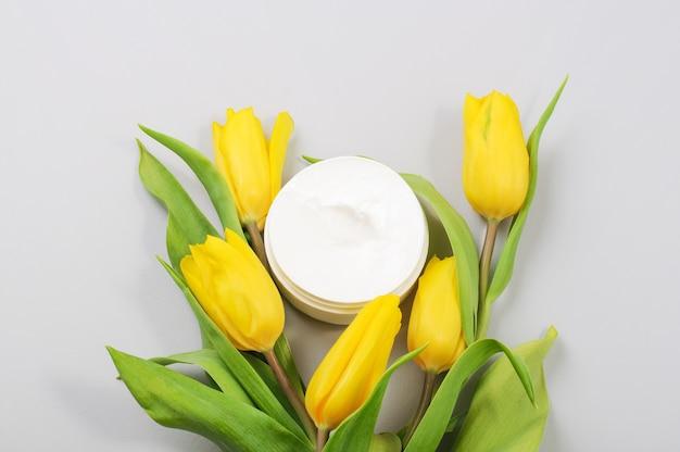 Hidratante natural orgânico com flores amarelas. creme hidratante em um frasco de flores.