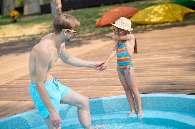 Hidrofobia. um pai tentando levar a menina assustada para a piscina