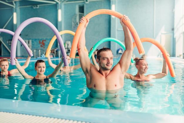 Hidroginástica aeróbica, mulher com treinador masculino, piscina coberta.