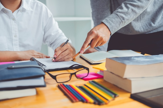 High school ou estudantes universitários estudando e lendo juntos na biblioteca