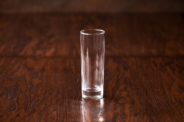 Highball de vidro vazio na mesa de madeira escura