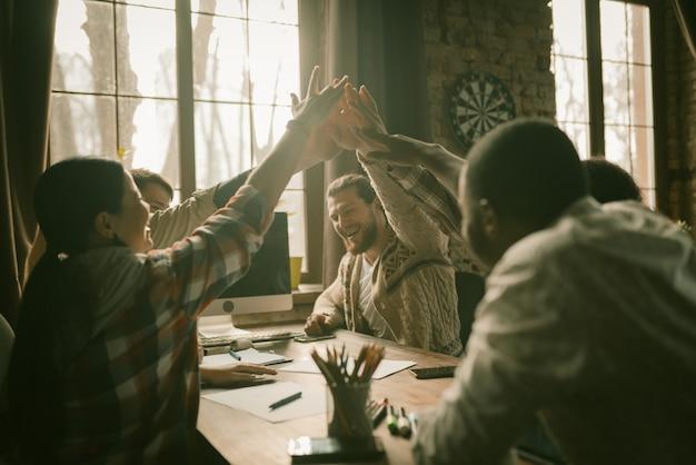 Highfive gesto da equipe de freelancers felizes