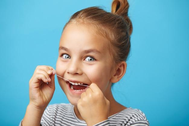 Higiene bucal e cuidados com a saúde. menina sorridente criança usar fio dental dentes saudáveis brancos.