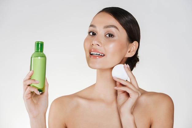Higiene da manhã e beleza da jovem mulher com pele saudável macia, limpeza de rosto com loção e algodão, isolado sobre o branco
