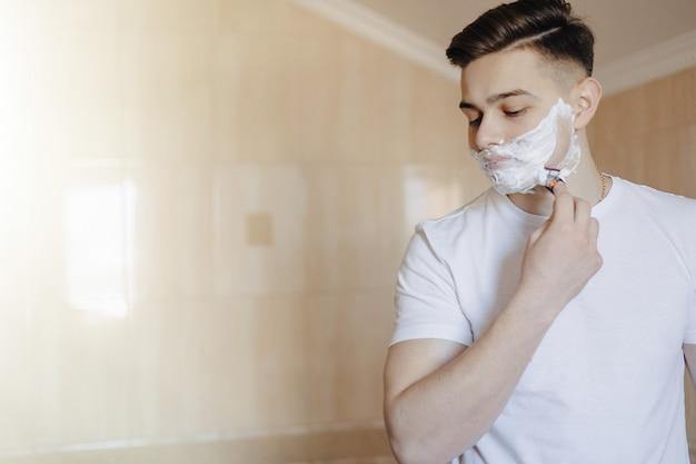 Higiene da manhã, o homem faz a barba com espuma