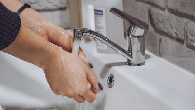 Higiene das mãos. como lavar as mãos com água e sabão. mulheres que lavam as mãos com sabão antibacteriano em casa banheiro. impedir a propagação de germes.