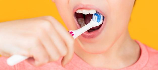 Higiene dental. homenzinho escovando os dentes. menino de criança criança feliz com escova de dentes. cuidados de saúde, higiene dental