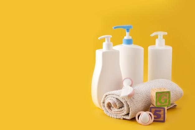 Higiene do bebê e utensílios de banho na superfície amarela
