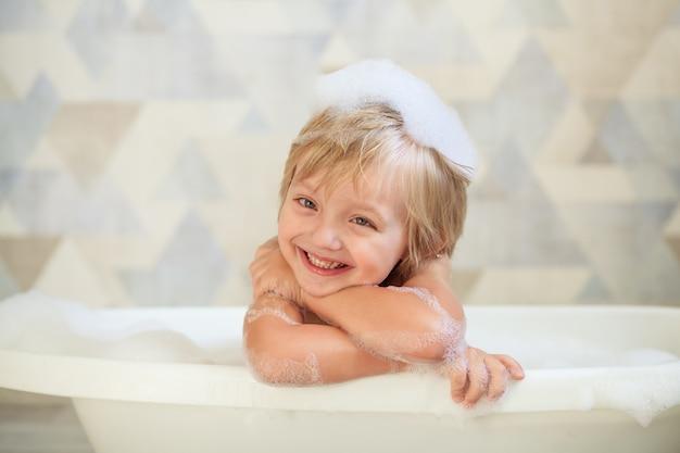 Higiene infantil. a criança toma banho em um grande banho. menino bonito feliz 4-5 anos de idade com espuma no cabelo.