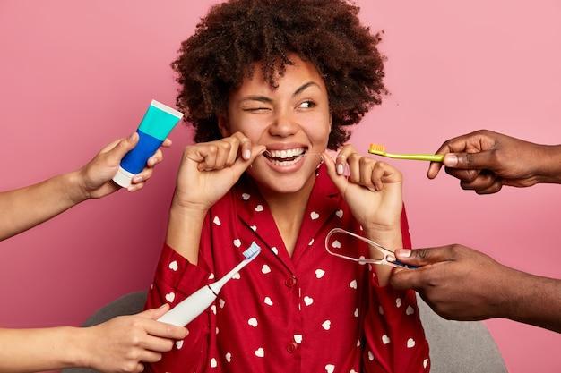 Higiene oral e conceito de cuidados com os dentes. mulher de cabelo encaracolado limpa os dentes com fio dental, limpa a língua com limpador, usa escova e pasta de dente, posa em casa