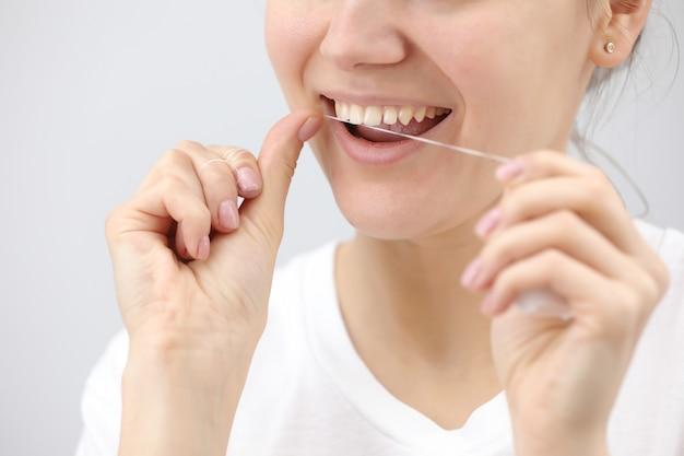 Higiene oral e cuidados de saúde. mulheres sorridentes usam fio dental de dentes brancos e saudáveis