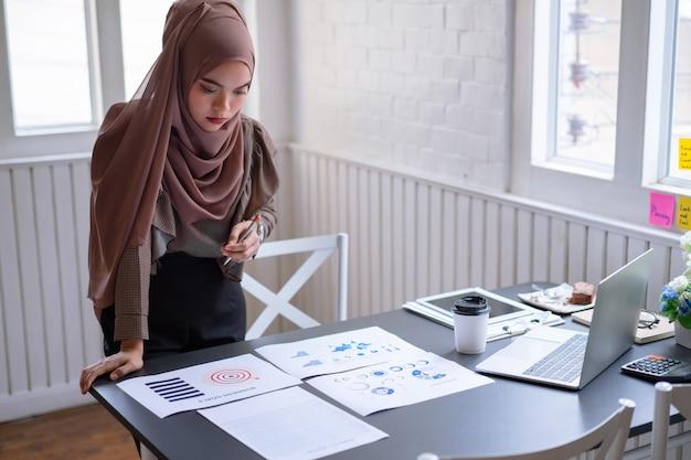 Hijab árabe profissional do marrom da mulher de negócios que está e que verifica no relatório da carta do gráfico do projeto de investimento financeiro.