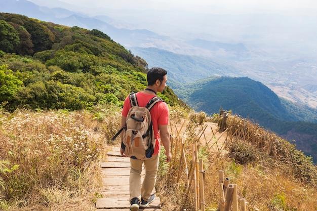 Hiker em um caminho de madeira na região montanhosa