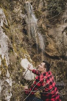 Hiker escalando ao lado de uma cachoeira