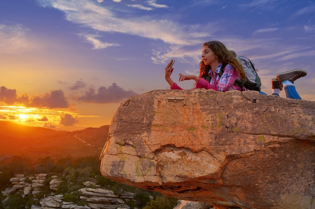 Hiker girl teen selfie telefone no pico da montanha