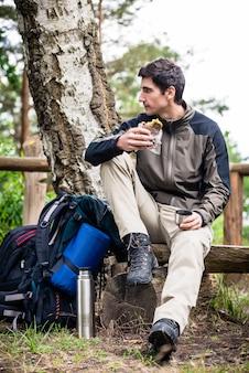Hiker, levando, alimento, partir, sombra, de, árvore