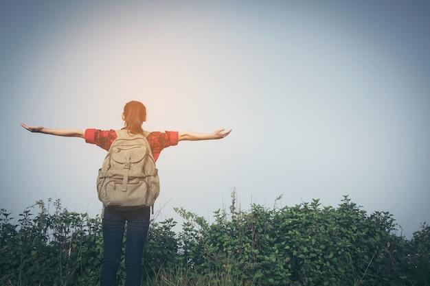 Hiker mulher procura binóculos na montanha, fundo céu azul, tailândia, selecione e foco suave