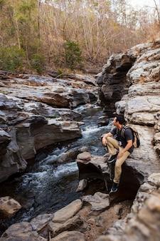 Hiker sentado ao lado do rio selvagem