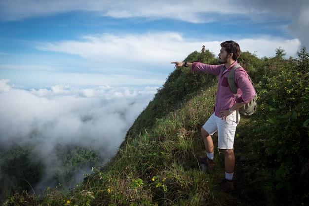 Hikers com mochilas relaxando no topo de uma montanha e desfrutando a vista do vale