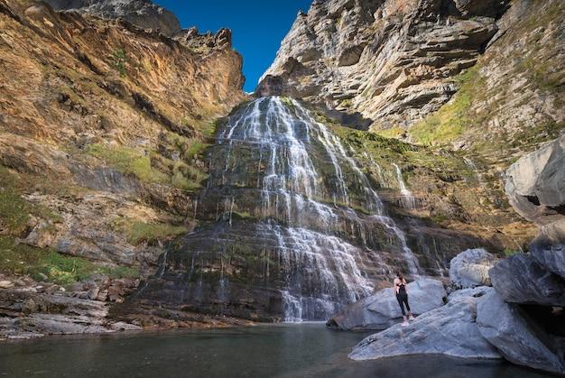 Hikker womann que olha a cachoeira do horsetail no parque nacional de ordesa, pyrenees, espanha.