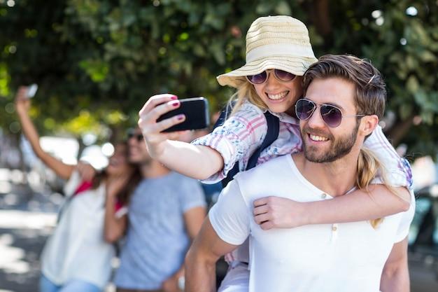 Hip homem dando piggy volta para sua namorada e tomando selfie na rua