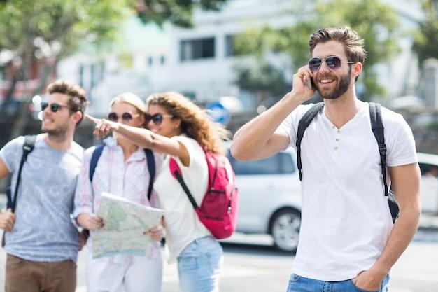 Hip homem no telefonema e amigos verificando o mapa ao ar livre