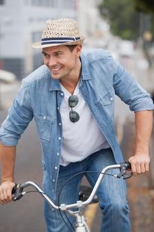Hip jovem em jeans em sua bicicleta