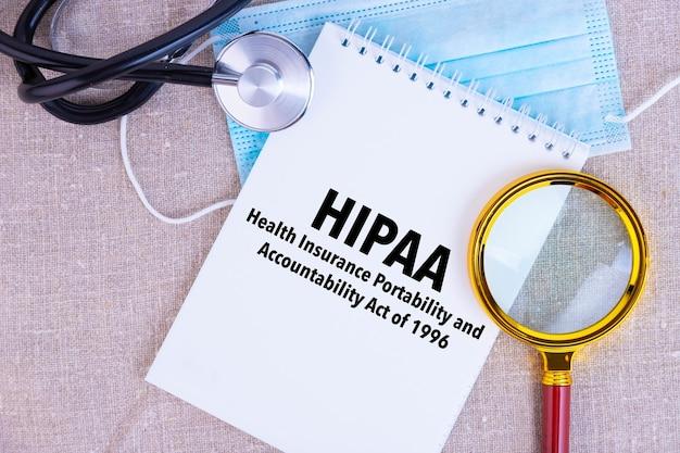 Hipaa, a lei de responsabilidade e portabilidade de seguro saúde de 1996, texto escrito em um bloco de notas branco, máscara médica, estetoscópio, lupa sobre fundo de linho.