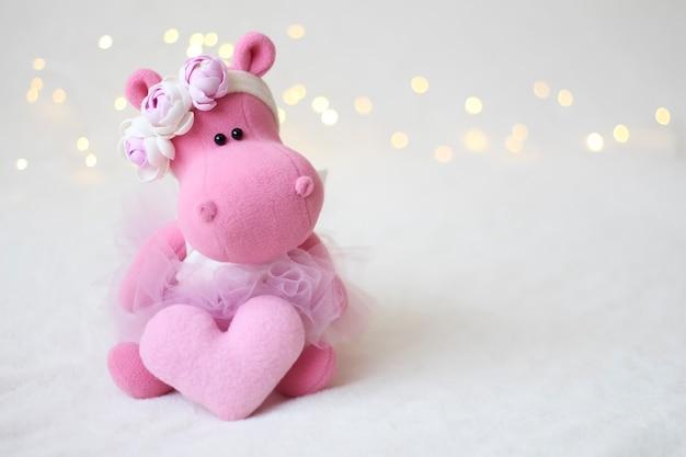 Hipopótamo rosa, composição de primavera com flores e festão.