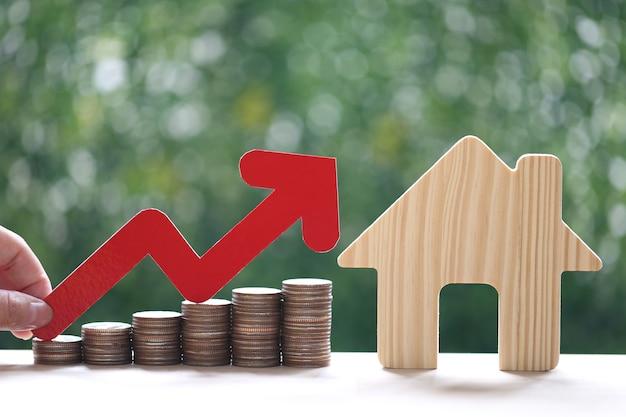 Hipoteca, mão de uma mulher segurando um gráfico de seta vermelha e uma pilha de moedas de dinheiro com a casa modelo em fundo verde natural, investimento empresarial e conceito imobiliário