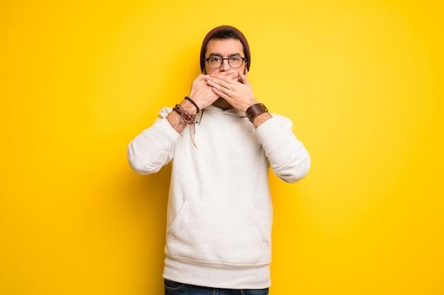 Hippie homem com dreadlocks cobrindo a boca com as mãos para dizer algo inadequado