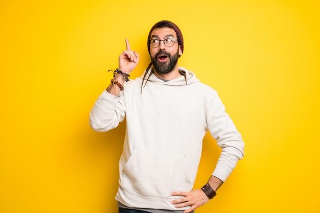 Hippie homem com dreadlocks com a intenção de perceber a solução enquanto levanta um dedo