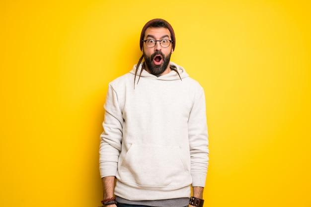 Hippie homem com dreadlocks com surpresa e expressão facial chocada