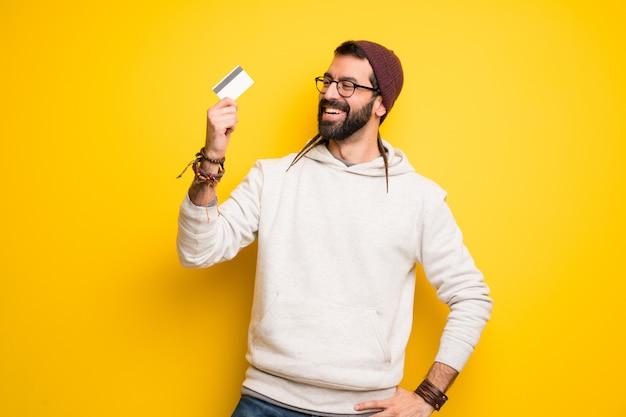 Hippie homem com dreadlocks segurando um cartão de crédito e pensando