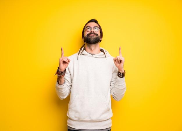 Hippie homem com dreadlocks surpreso e apontando para cima