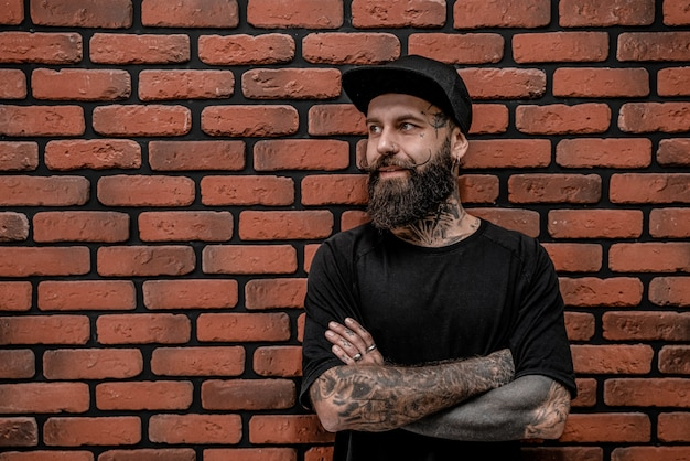 Hipster à moda antiga bonito em t-shirt e boné, pose com os braços cruzados. isolado em um fundo de tijolo.