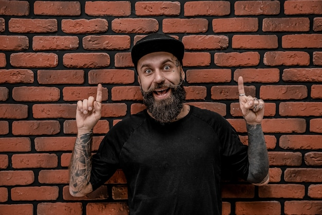 Hipster à moda antiga bonito em t-shirt e boné, pose engraçada e sorria. em um fundo de tijolo.