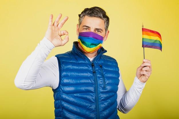 Hipster alegre com máscara e bandeira do orgulho gay fazendo gestos com as mãos ok