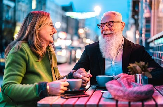 Hipster aposentado casal sênior apaixonado, bebendo café no café bar ao ar livre