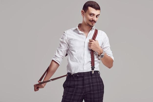 Hipster árabe jovem bonito com camisa branca e suspensórios
