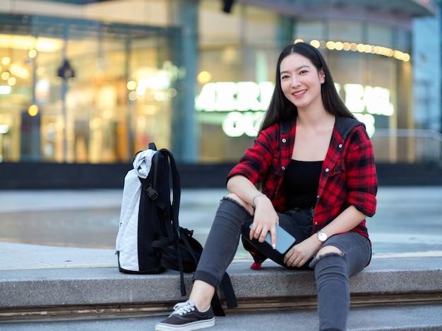 Hipster atraente jovem viajante solo com mochila sentado na escada em frente ao centro da cidade