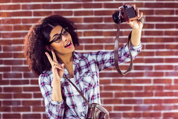 Hipster atraente que toma selfies com câmera