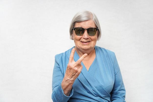 Hipster avançado de vovó em óculos de sol da moda mostrando gesto de dois dedos