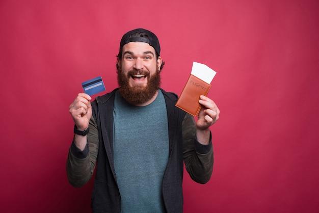 Hipster barbudo alegre está segurando seu passaporte e cartão de crédito em rosa vermelho