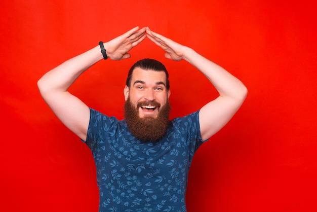 Hipster barbudo animado está fazendo o gesto do telhado da casa.