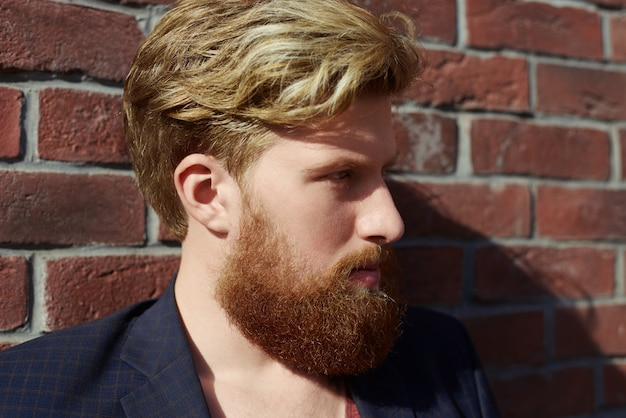 Hipster barbudo bonito com emoção séria na parede de tijolo vermelho