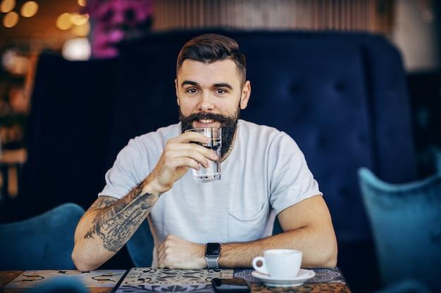 Hipster barbudo caucasiano sorridente sentado no café pela manhã, bebendo água