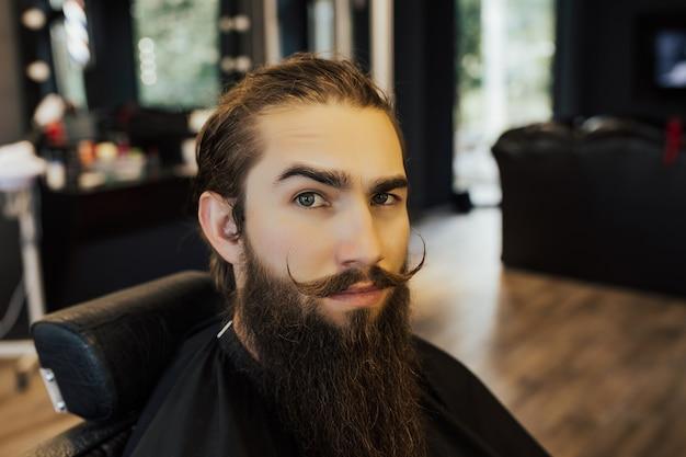 Hipster barbudo de homem na barbearia da moda elegante.